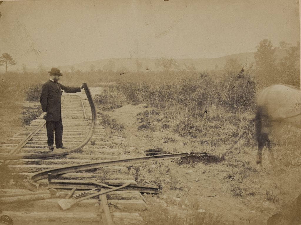 Military railroad operations in northern Virginia: man standing on railroad tracks holding twisted rail