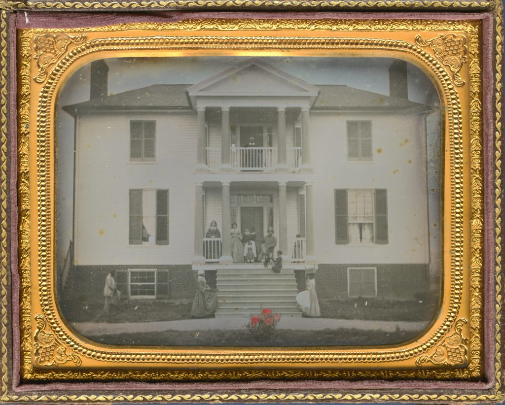 Enslaved household servants pose with white owners in front of a columned plantation house