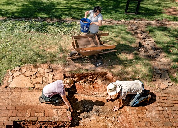 Overhead shot of three people at work on an archaeological dig at James Monroe's Highland
