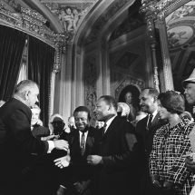 President Lyndon B. Johnson reaches out to shake Dr. Martin Luther King's hand