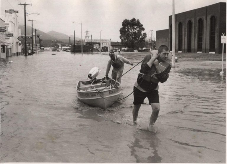 Man pulling a small boat through a flooded street in Buena Vista