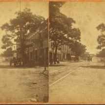 Unpaved Cotton Avenue in Macon, Georgia, with a trolley and local businesses