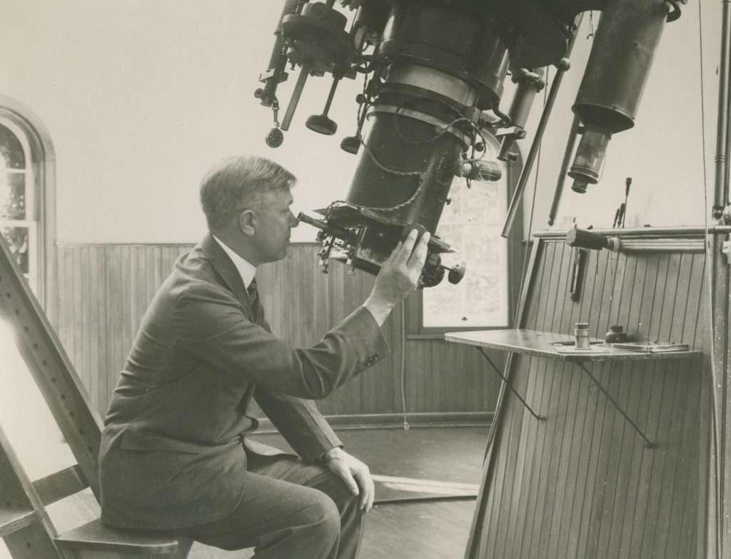 Man adjusting lens of a large telescope